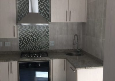 Anchor Property Group - kitchen renovation black and silver tile wall and hob